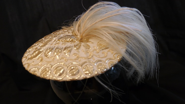 Gold ponytail saucer hat by Nick Savage.